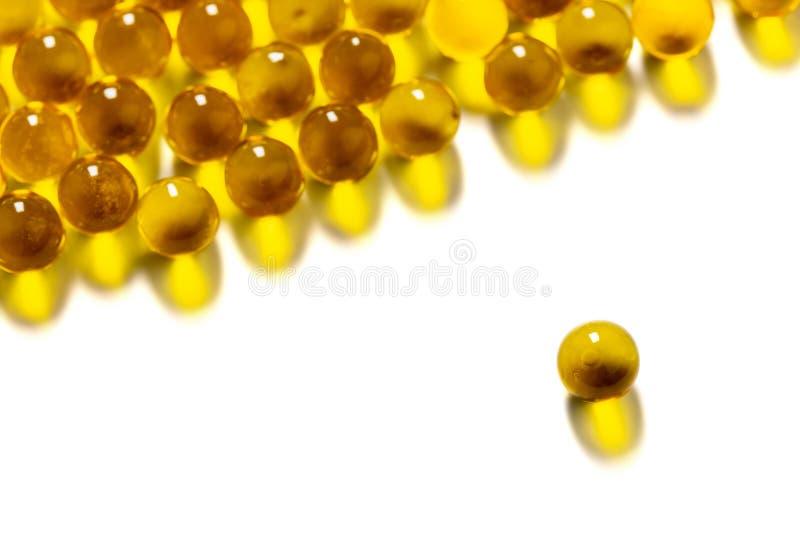 Cápsulas esféricas anaranjadas de la bola de foco selectivo del aceite de pescado aislado en el fondo blanco foto de archivo libre de regalías