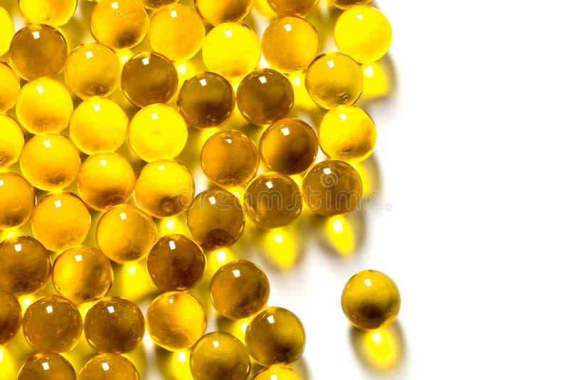 Cápsulas esféricas anaranjadas de la bola de foco selectivo del aceite de pescado aislado en el fondo blanco fotos de archivo libres de regalías