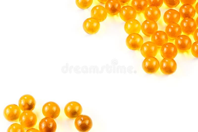 Cápsulas esféricas anaranjadas de la bola de foco selectivo del aceite de pescado en el fondo blanco fotos de archivo