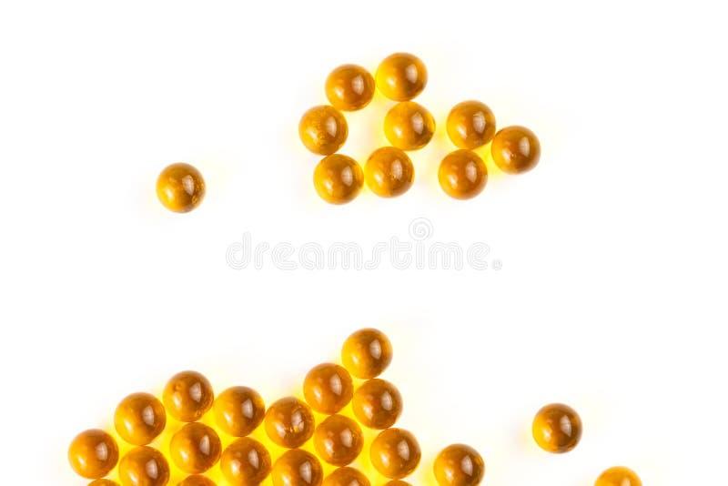 Cápsulas esféricas anaranjadas de la bola de foco selectivo del aceite de pescado en el fondo blanco imagen de archivo