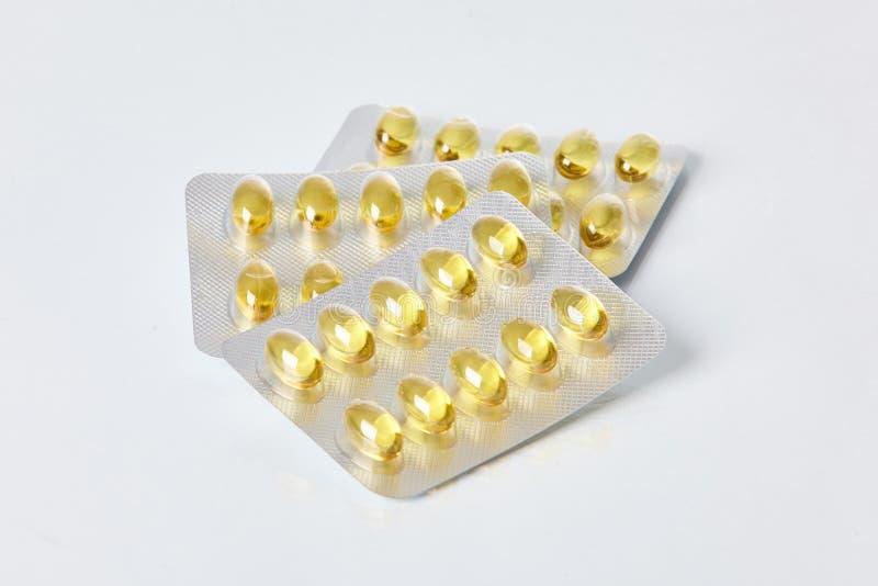 Cápsulas gelatinosas del aceite de pescado en paquete de ampolla en el fondo blanco imágenes de archivo libres de regalías