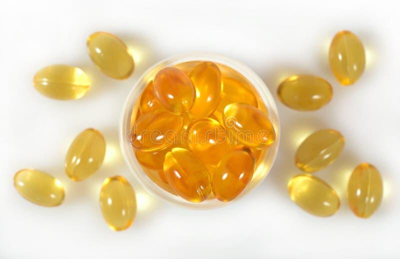 Cápsulas gordas do óleo dos peixes Omega-3 em uma garrafa em um branco foto de stock royalty free