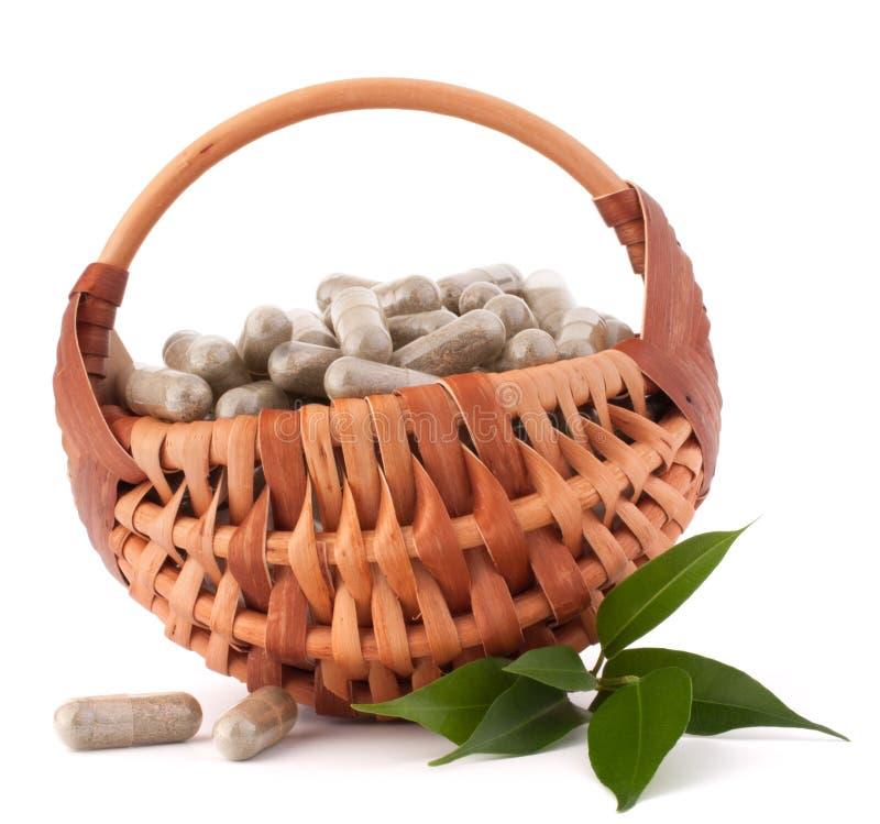 Cápsulas herbarias de la droga en cesta de mimbre. Medicina alternativa concentrada imágenes de archivo libres de regalías