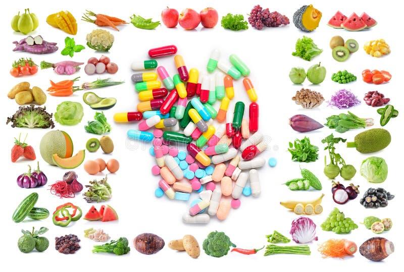 Cápsulas médicas, fruta y verdura aislada en el backgroun blanco foto de archivo libre de regalías