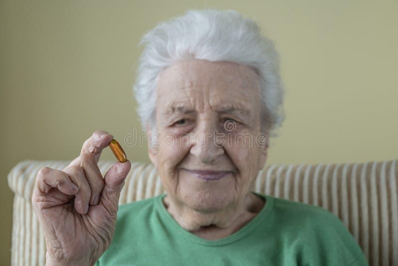 Cápsulas mayores preciosas de la mujer de una vitamina de la tenencia fotos de archivo libres de regalías