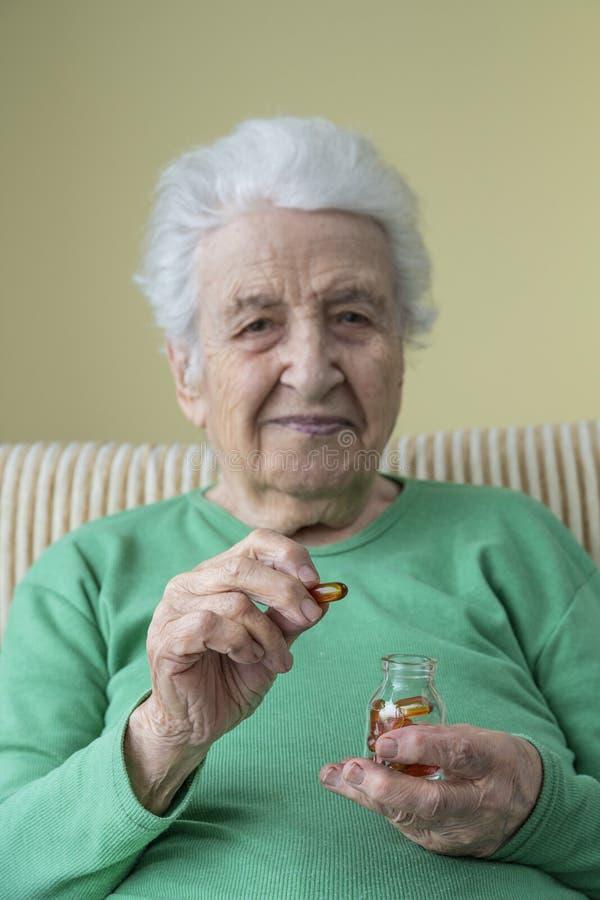 Cápsulas mayores preciosas de la mujer de una vitamina de la tenencia fotografía de archivo