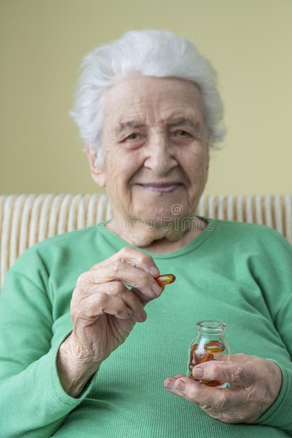 Cápsulas mayores preciosas de la mujer de una vitamina de la tenencia fotografía de archivo libre de regalías
