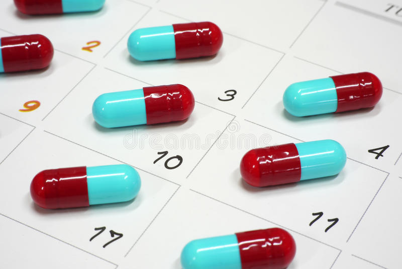 Cápsulas vermelhas e azuis no calendário imagem de stock royalty free