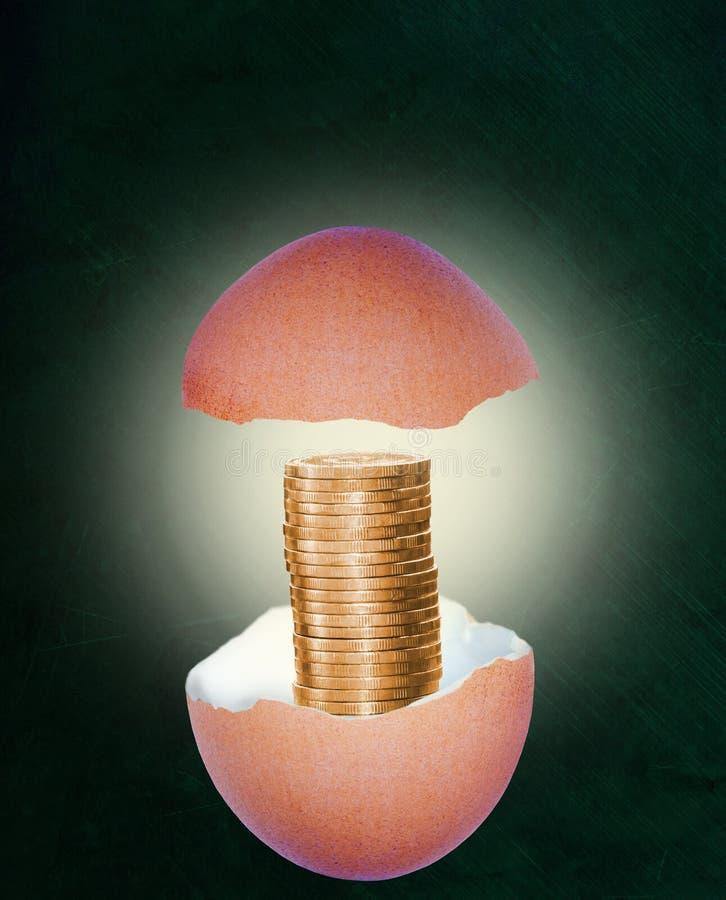 Cáscara de huevo quebrada con la pila de monedas de oro en concepto de los ahorros del retiro fotografía de archivo libre de regalías