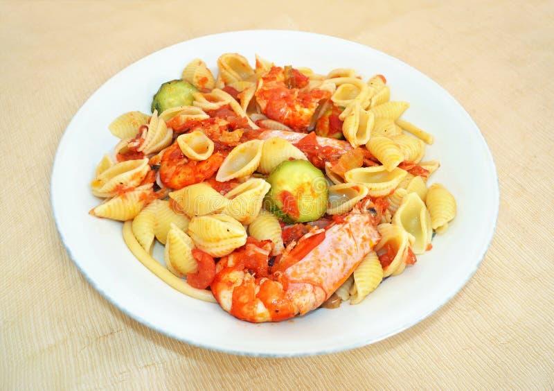 Cáscara de las pastas con los camarones y la salsa de tomate imagenes de archivo