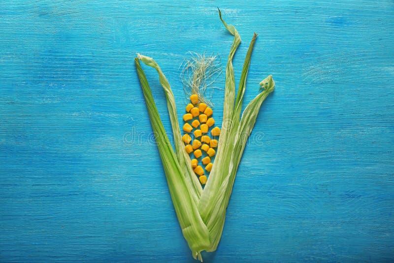 Cáscara de maíz con los corazones en la tabla de madera del color imagen de archivo libre de regalías
