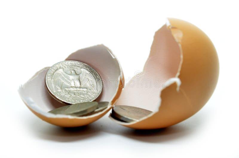 Cáscara y monedas agrietadas de huevo fotografía de archivo libre de regalías