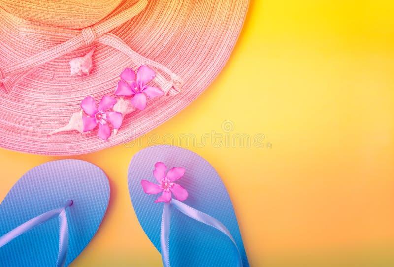 Cáscaras azules del mar de los deslizadores de las flores tropicales del rosa del sombrero de la paja de las mujeres en fondo ama imagenes de archivo