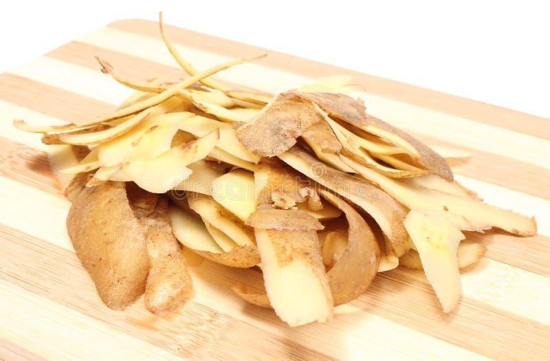 Cáscaras de patata que mienten en tabla de cortar de madera imagen de archivo