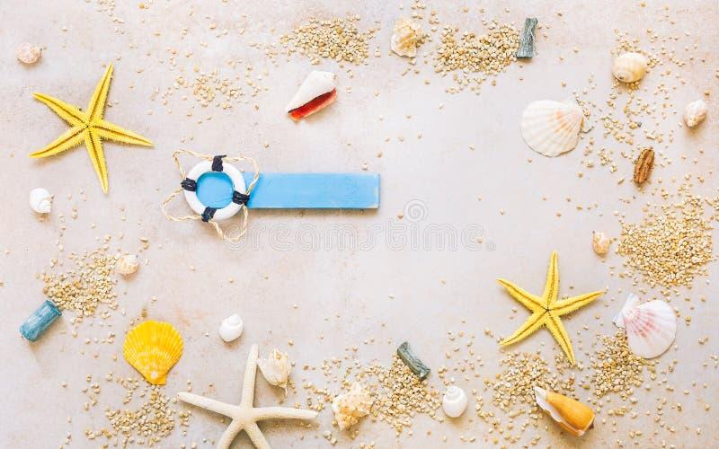 Cáscaras del mar con la arena y artículos marinos como fondo imagenes de archivo