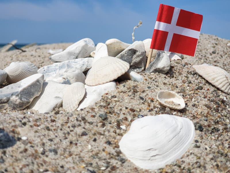 cáscaras, piedras blancas y una bandera danesa foto de archivo