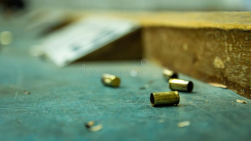 Cáscaras vacías de la bala de la pistola en la tabla de madera en una radio de tiro foto de archivo libre de regalías