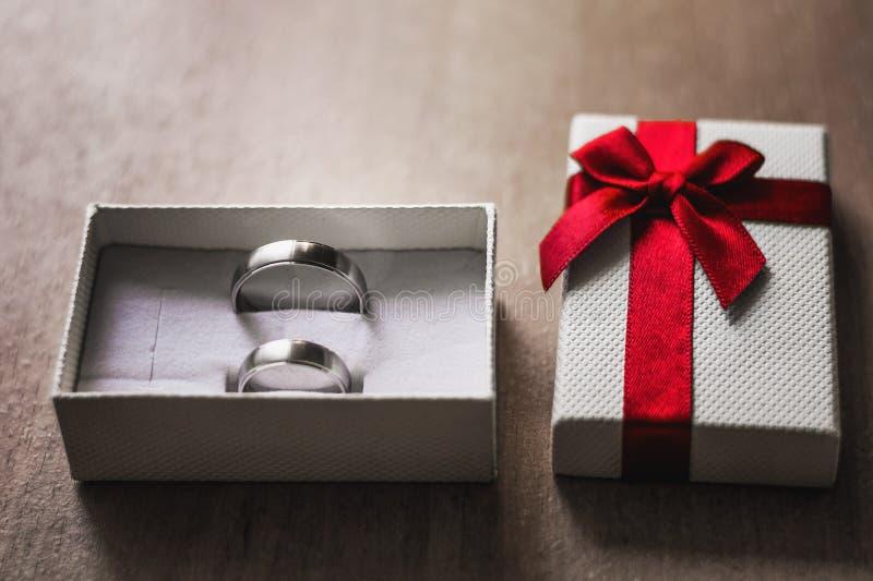 Cáseme concepto Caja blanca con dos anillos de compromiso foto de archivo