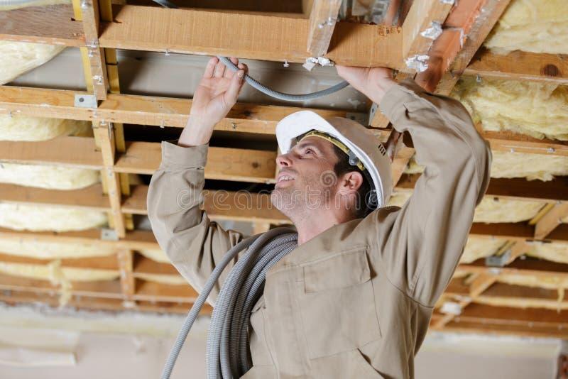 Câblage masculin de constructeur à l'intérieur de plafond images stock