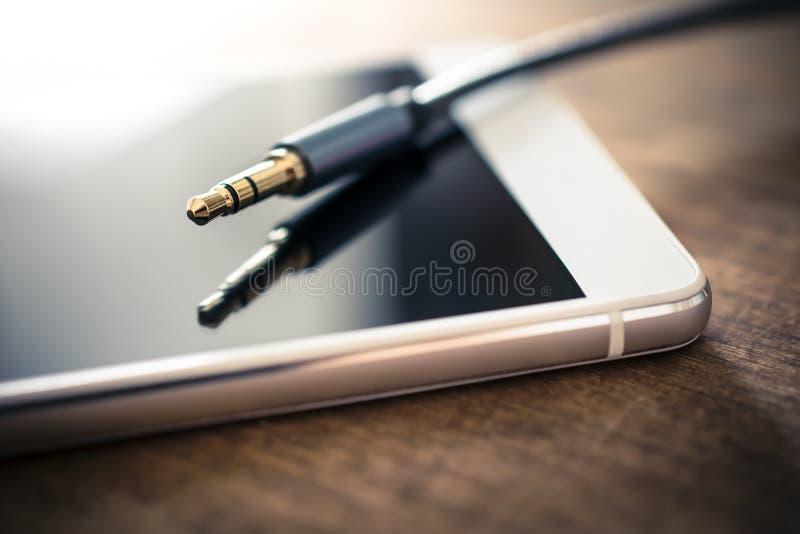 Câble d'écouteur branché, se trouvant sur Smartphone blanc sur le Tableau en bois images stock