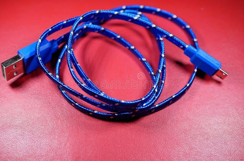 Câble d'USB dans la tresse bleue avec les points blancs sur le fond rouge images libres de droits