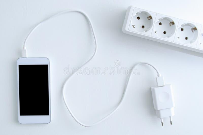 Câble de chargement de batterie de smartphone et prise de courant blancs photographie stock