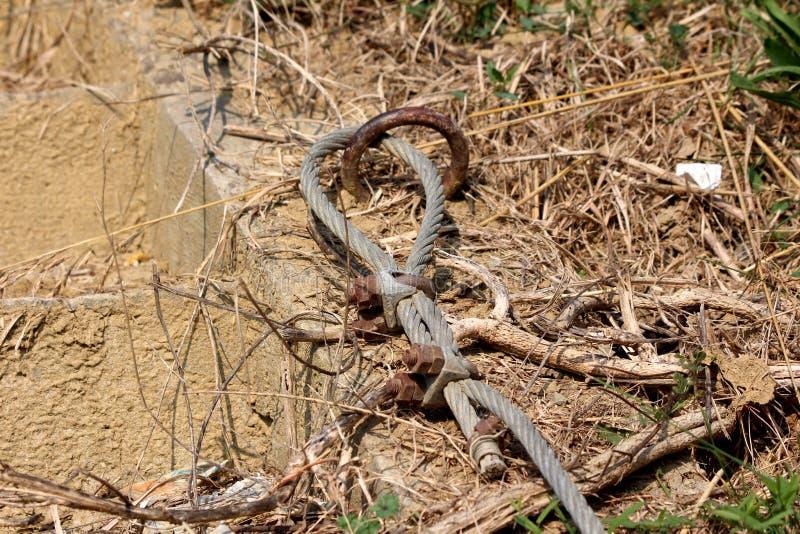 Câble fort en métal relié à l'anneau rouillé établi dans la base concrète et tenu en place aux vis et aux boulons entourés à images stock