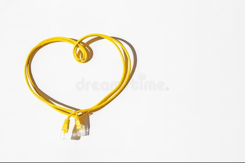 Câble jaune de réseau plié sous forme de coeur d'isolement sur le blanc Journée de sécurité d'Internet Télécommunication et infor images libres de droits