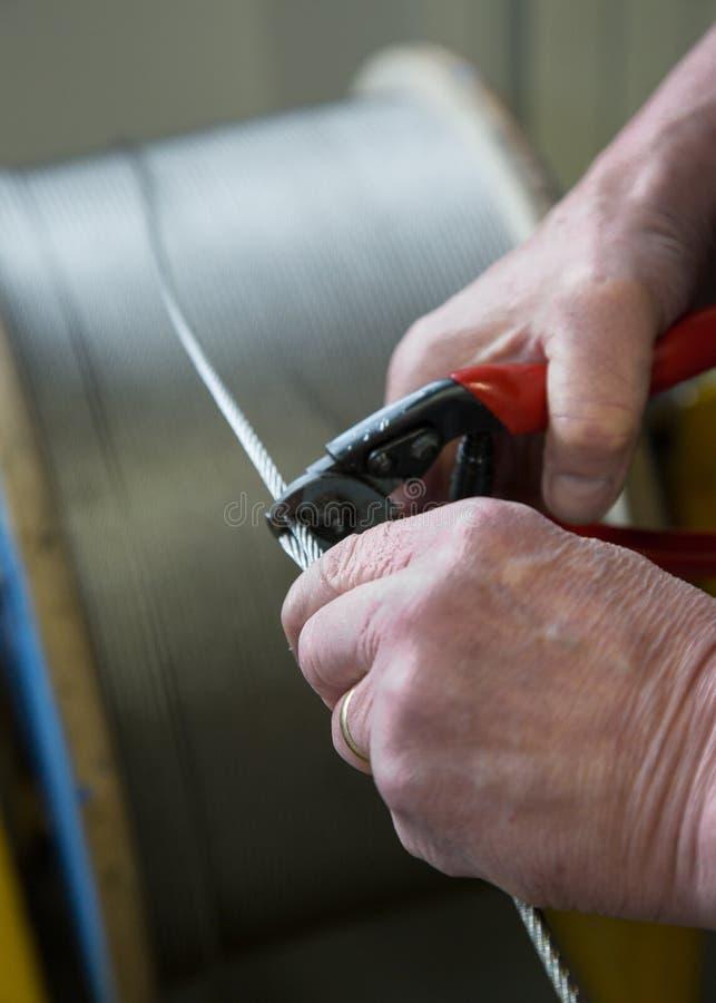 Câble métallique de coupe à la main images stock