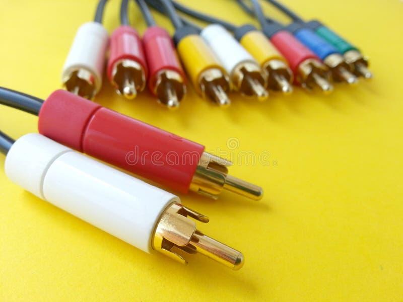 Câble visuel audio de rca de communication sur un fond jaune image stock