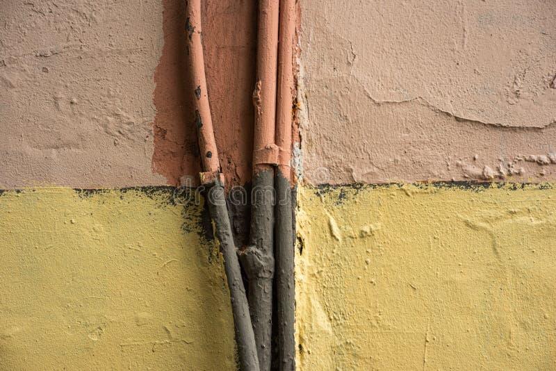 Câbles anciens peints sur le mur jaune et rouge d'un immeuble photographie stock libre de droits