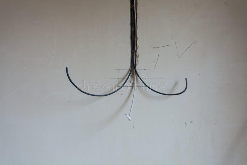 Câbles pour la TV, l'ordinateur et tout autre équipement à la maison dans le mur en béton de l'appartement qui est en constructio image stock