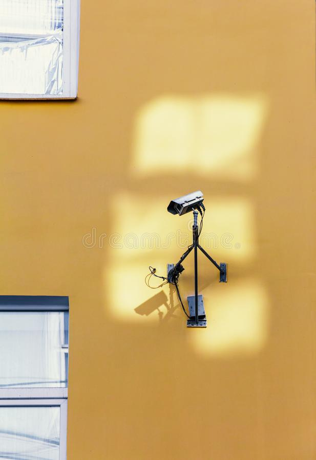 Câmara de segurança na parede amarela foto de stock