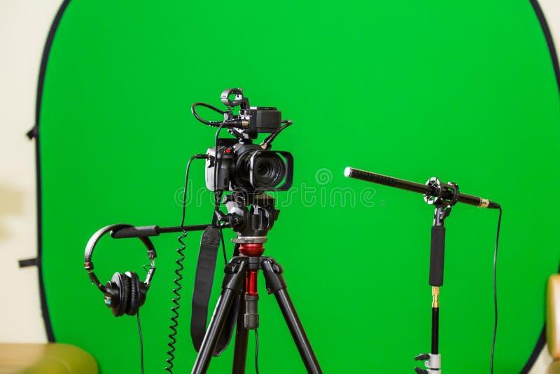 Câmara de vídeo em um tripé, em fones de ouvido e em um microfone direcional em um fundo verde A chave do croma Tela verde fotografia de stock royalty free