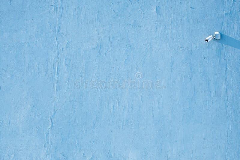 Câmara de vídeo para a observação no canto do quadro na parede coberta com o emplastro fora do azul imagens de stock royalty free