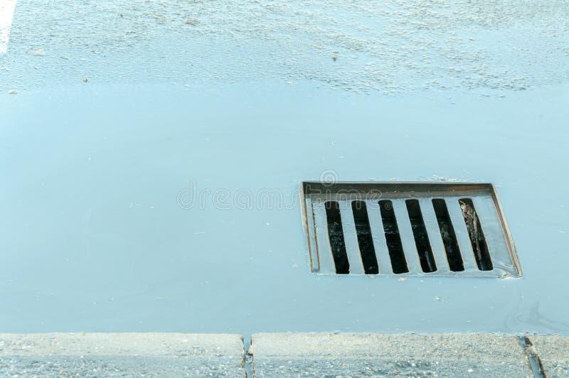 Câmara de visita da drenagem da rua com água após a chuva que vai dentro imagem de stock royalty free