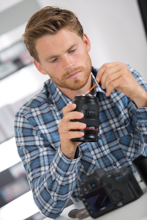 Câmara digital da lente da limpeza do homem com escova especial imagem de stock royalty free
