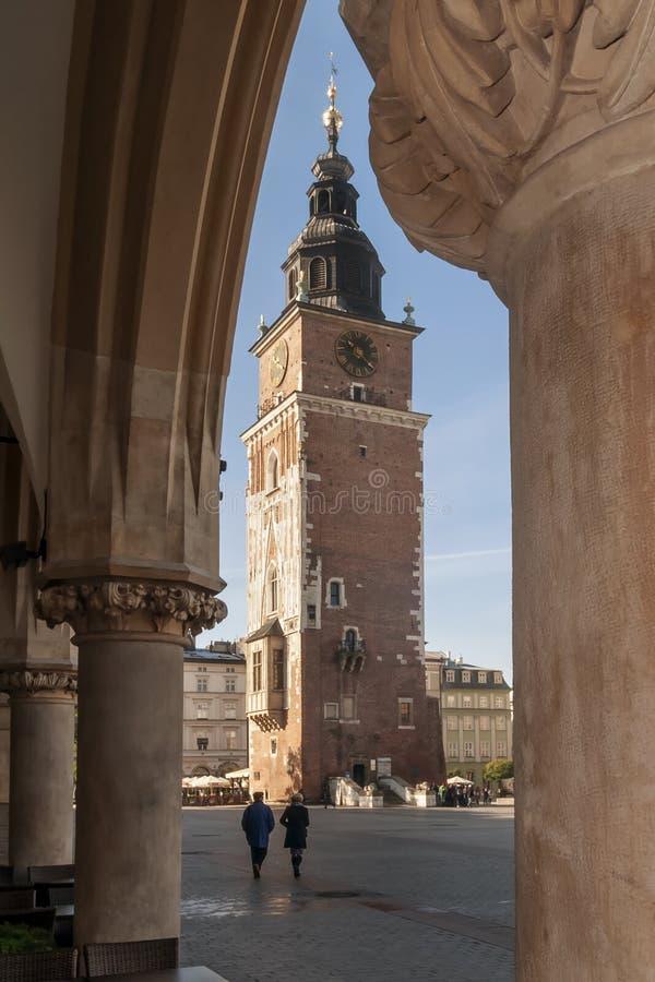 A câmara municipal da torre quadro pelas colunas do mercado central de Krakow, Polônia imagem de stock