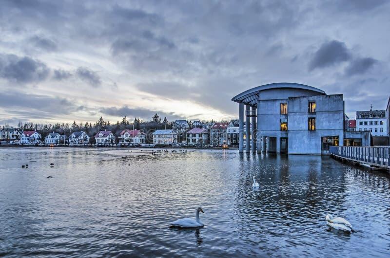 Câmara municipal e lago de Reykjavik sob um céu dramático foto de stock royalty free