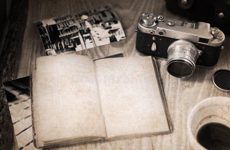 Câmera antiquado, livro aberto, xícara de café imagem de stock royalty free