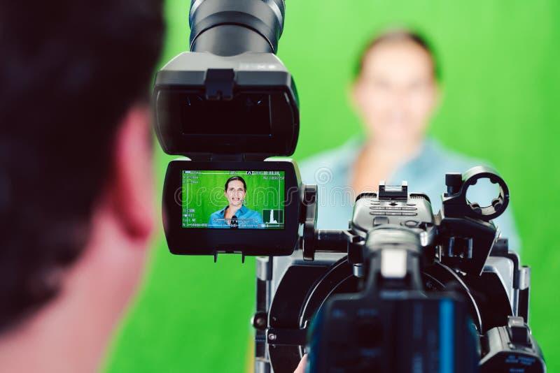 A câmera apontou em uma mulher ou em um repórter da notícia no estúdio verde da sala fotos de stock
