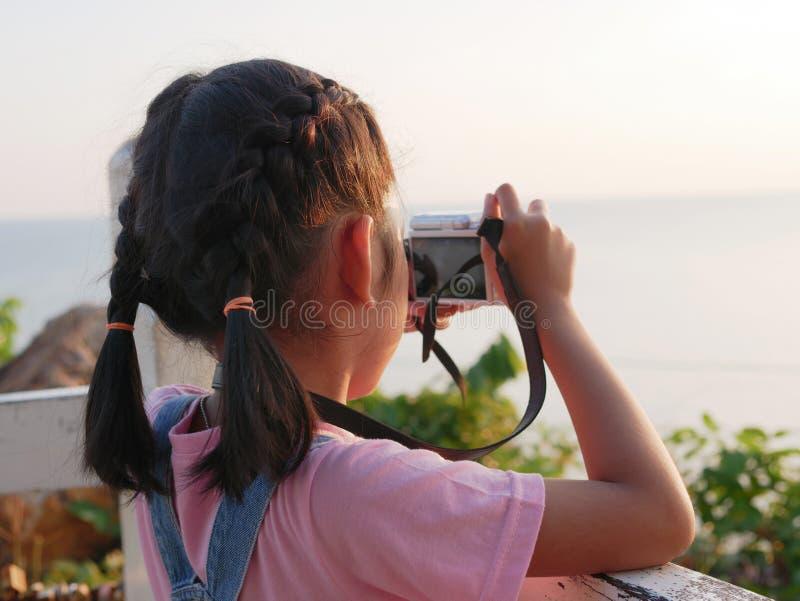 Câmera asiática da terra arrendada da menina que toma uma imagem com viagem na natureza imagem de stock