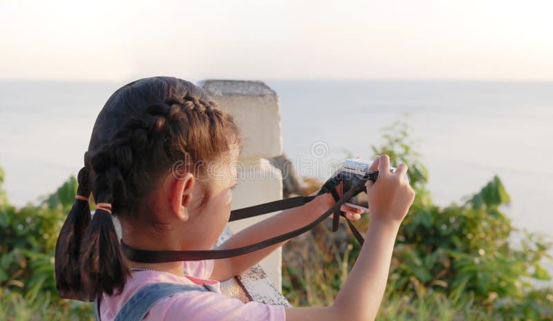 Câmera asiática da terra arrendada da menina que toma uma imagem com viagem, smilling e felicidade na natureza imagens de stock