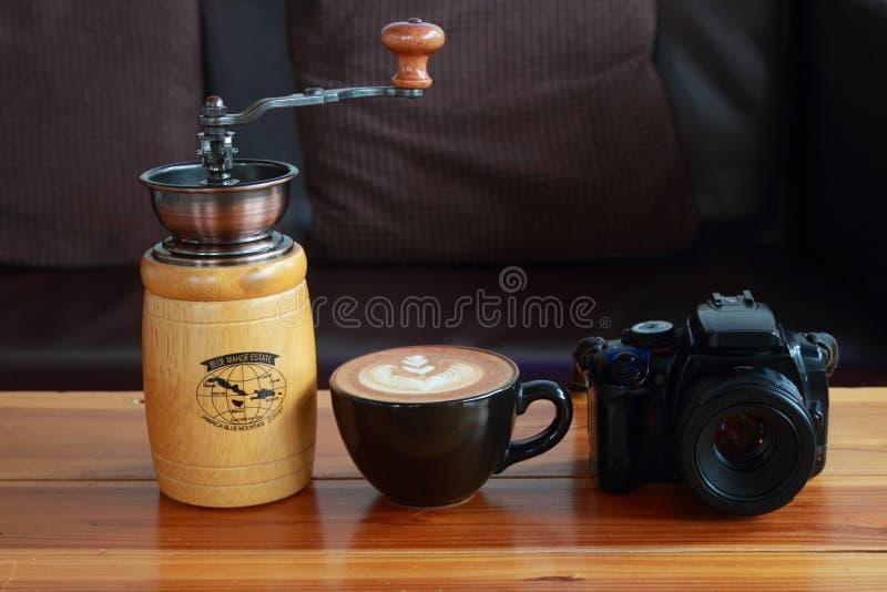 câmera, café do vintage e moedor de café marrons no ouro de madeira fotos de stock royalty free