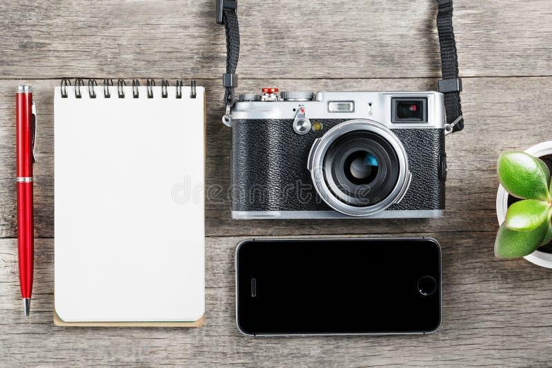 Câmera clássica com a página vazia do bloco de notas e pena vermelha em de madeira cinzento, mesa do vintage com telefone imagem de stock royalty free