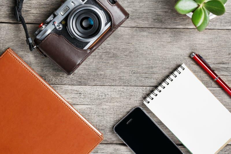 Câmera clássica com a página vazia do bloco de notas e pena vermelha na tabela cinzenta de madeira, do vintage com telefone e na  foto de stock royalty free
