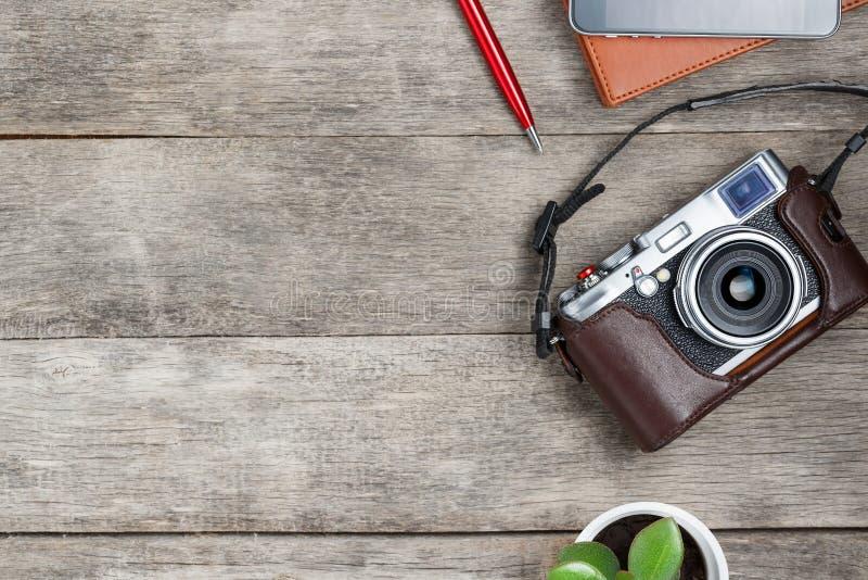 Câmera clássica em um fundo de madeira cinzento, com um bloco de notas marrom, uma pena vermelha, um telefone e crescimento verde fotografia de stock