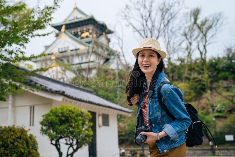 Câmera da cara do turista da moça que sorri guardando a câmera do slr do fotógrafo curso profissional sempre com seu digicam Viaj fotos de stock royalty free