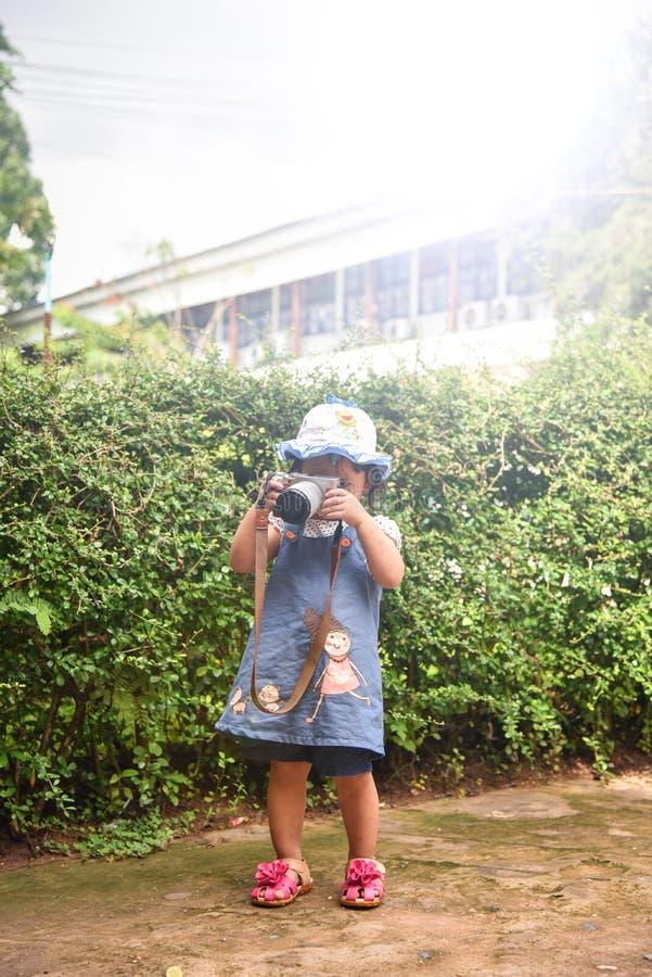 A câmera da criança toma a fotografia da foto a criança nova do fotógrafo que toma fotos com câmera imagem de stock
