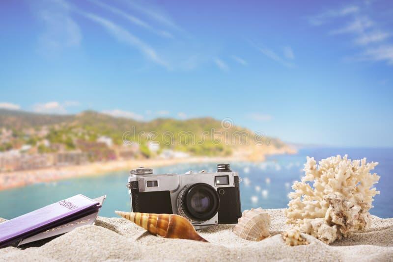 Câmera da foto com passaportes e conchas do mar na praia da areia no recurso fotografia de stock royalty free
